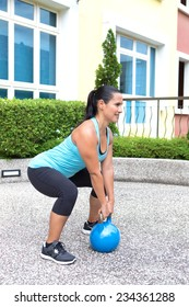 Beautiful sporty hispanic woman in blue training with kettlebell doing dead lift