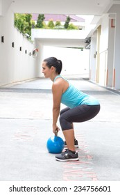 Beautiful sporty hispanic woman in blue attire holding a blue kettlebell in dead lift post outdoors