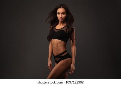 Beautiful sporty lady in black bikini with flying hair against dark background