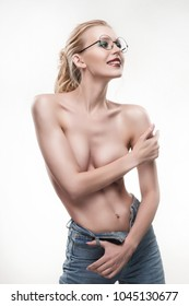Beautiful sporty naked shoulders young girl wearing round glasses and blue jeans covers her topless breasts with her hands isolated on white. Copy space. Advertising, conceptual and commercial design