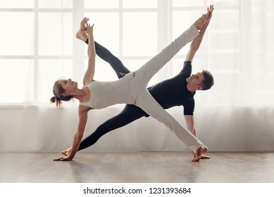 Beautiful sporty pair practicing yoga together at home