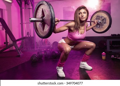 beautiful sporty sexy woman doing squat workout in gym