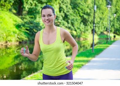 beautiful sporty slim woman running in summer park