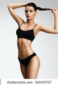 Beautiful sporty woman in black bikini posing on grey background. Photo of girl with slim toned body. Beauty and body care concept