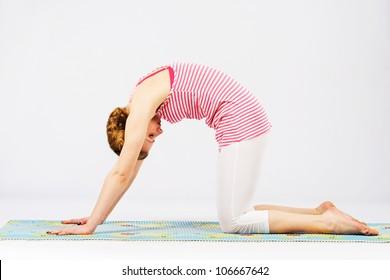 Beautiful sporty woman doing cat yoga pose. Bidalasana.