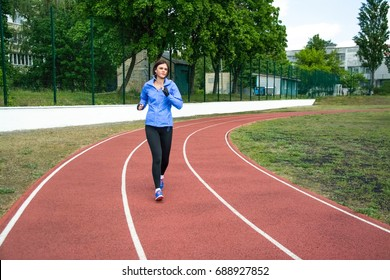 beautiful sporty woman doing exercises on the green lawn, dressed in sports clothes. gymnastics in the open air. sport in the big city