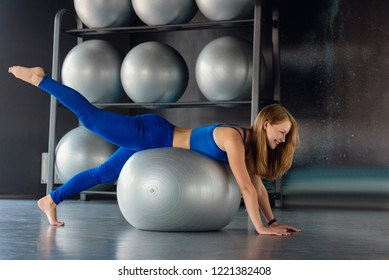Beautiful sporty woman doing pilates exercises with fitball