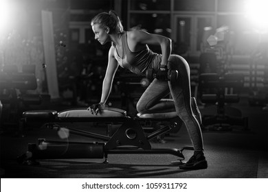 Beautiful sporty woman doing power fitness exercise at sport gym. Girl with dumbbell black and white.