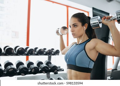 Beautiful sporty woman doing power fitness exercise at sport gym. Serious girl working with dumbbells. She is sitting near the window and listening to music. Close up