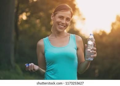 Beautiful sporty woman drinking water during exercise.Image is intentionally toned.