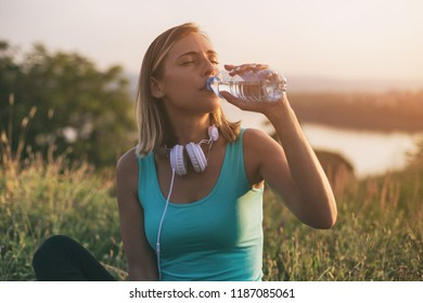 Beautiful sporty woman drinking water while sitting on exercise mat with a cityscape and river behinde her.Image is intentionally toned.
