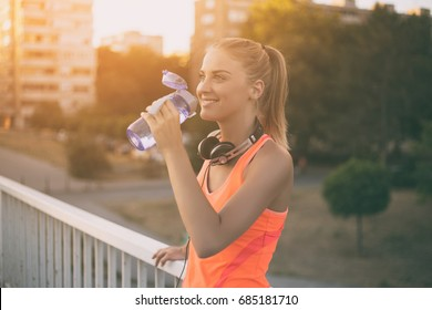 Beautiful sporty woman drinking water while resting from exercise.Refreshment after practicing Image is intentionally toned.