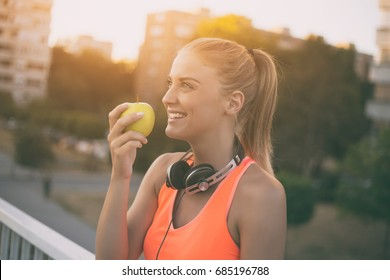 Beautiful sporty woman eating apple while resting from exercise.Healthy snack for fitness girl Image is intentionally toned.