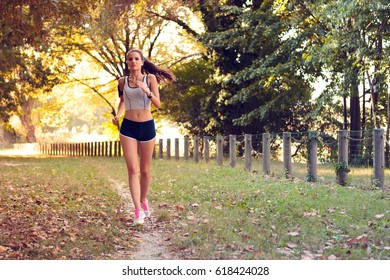 Beautiful sporty woman listening to music with earphones while jogging at park in sunrise light