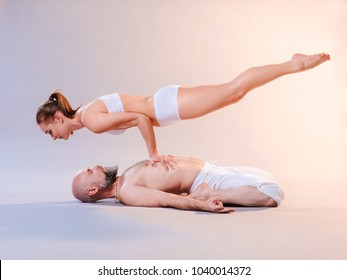 Beautiful sporty woman and man in white clothes doing yoga asanas together indoor