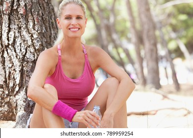 Beautiful sporty woman resting from exercising in nature forest countryside, sitting drinking mineral water bottle, looking smiling. Fitness, wellness well being sport activities. Training outdoors.