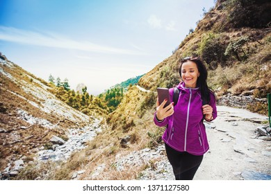 Beautiful sporty woman using her phone while trekking outdoors in Dharamsala, India