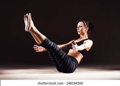 Beautiful sporty woman is working out. Paripurna Navasana. Full Boat Pose.
