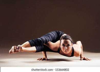 Beautiful sporty woman is working out. Eight-angle pose, Astavakrasana