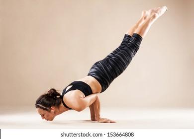 Beautiful sporty woman is working out. Peacock pose. Mayurasana.