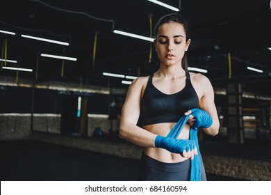 Beautiful sporty woman wrapping her fists with blue bandage tape. Fit girl is standing in gym and preparing to the fight. Close up