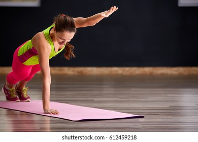 Beautiful sporty women practicing the yoga pose during a class in a gym