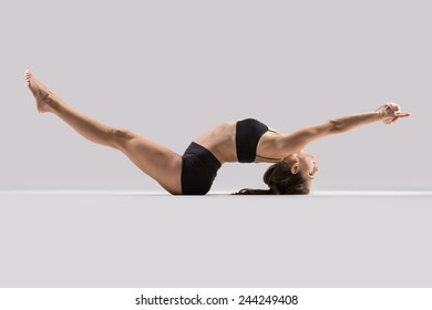 Beautiful sporty yogi girl practices yoga asana, doing warming up exercises, stretching legs and arms, lying on back on grey background, low key shot