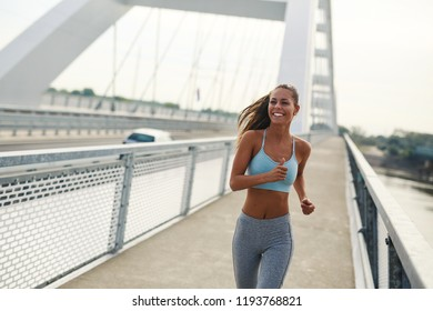 Beautiful sporty young woman running over bridge