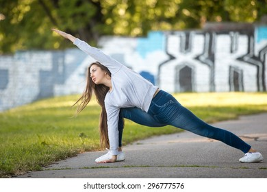 Beautiful sporty young woman working out on city street, doing warming up lunge exercise, Utthita Parsvakonasana, Extended Side Angle Pose, full length
