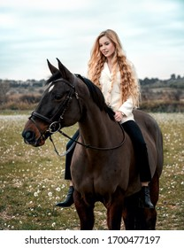 in a beautiful sprind season of a young girl and horse in a field. Beautiful long blonde hair girl with horse outdoors
