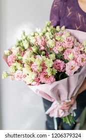 beautiful spring bouquet. Young girl holding a flowers arrangement with lisianthus of pink colors
