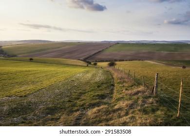 Beautiful Spring evening light over fields landscape on farm