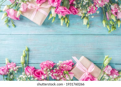 Beautiful spring flowers on light blue wooden background. Festive floral composition with craft paper  gift boxes. Valentine's day, Womans day, mothers day greeting card . Top view flat lay