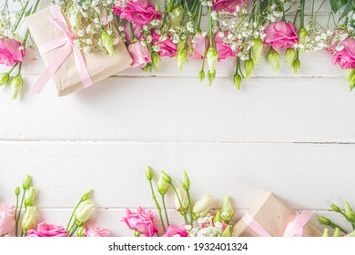 Beautiful spring flowers on white wooden background. Festive floral composition with craft paper  gift boxes. Valentine's day, Womans day, mothers day greeting card . Top view flat lay