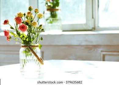 Beautiful spring flowers in vase on window background - Shutterstock ID 379635682