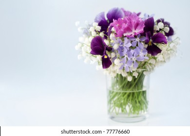 Beautiful spring flowers in a vase on white background