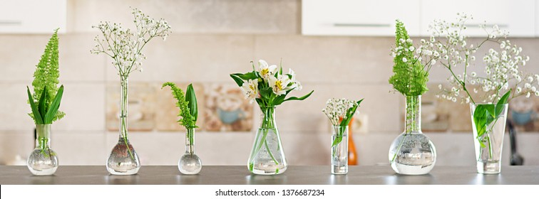 Beautiful spring flowers in a vases on light background. Banner