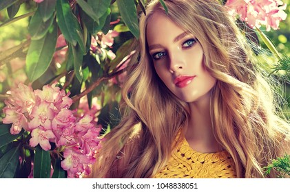 Beautiful spring   girl   in fragrant  pink  flowers  in summer blossom park. Woman in a blooming garden . Fashion, Cosmetics & Perfumes . Curly blonde hair