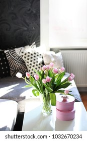beautiful spring image of spring centerpiece on white coffee teable with pink tulips in a glass vase