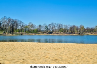 Beautiful spring landscape. Empty beach by the lake on a sunny day.