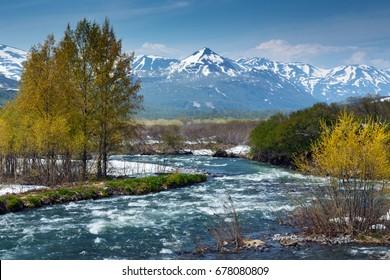 Beautiful spring landscape of Kamchatka Peninsula: stunning view of mountain Paratunka River on sunny daywith blue sky. Eurasia, Russian Far East, Kamchatka Region.