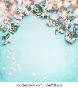 Schöner Frühlingshintergrund mit herrlicher Blüte, Blütenblatt und Bokeh auf türkisblauem Hintergrund, Draufsicht, Rahmen. Springtime-Konzept