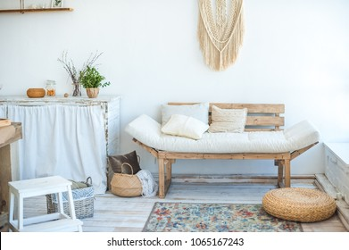 Beautiful spring photo of kitchen interior in light textured colors. Kitchen, living room with beige couch sofa, large cactus and woven macrame on the wall