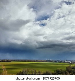 Beautiful spring scenery, bright Green field, naked trees, country road and distant Vidnoe city at the background of dramatic rainy sky, Moscow region, Russia