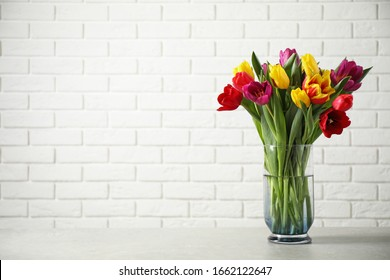 Beautiful spring tulips in vase on table near white brick wall. Space for text