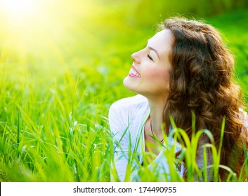 Beautiful Spring Young Woman Outdoors Enjoying Nature. Healthy Smiling Girl in Green Grass. Spring Meadow. Beautiful Lady Lying on the field