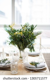 Beautiful springtime table setting with green leaves and mimosa branches, bright white table dinner decoration