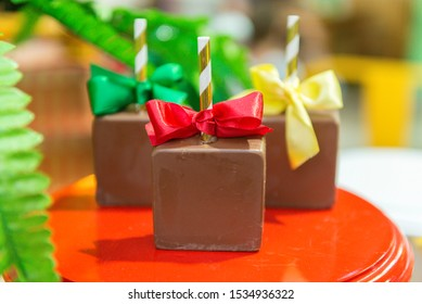 Beautiful square chocolate candies on a red tray. Sticks with colored bows. Selective focus.