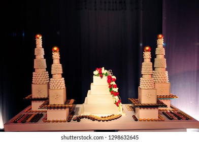 Beautiful square white wedding cake with draping red roses taking centre stage on a lavishly decorated desserts table.