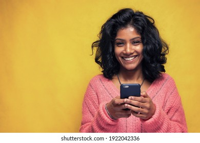 Beautiful Sri Lanka girl makes technology poses with yellow bright background - Young woman uses mobile phone to chatting and messaging - Shutterstock ID 1922042336